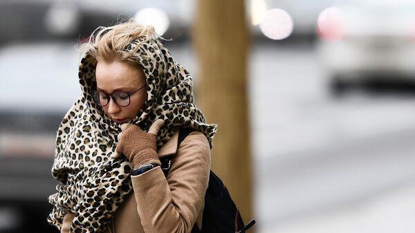 Женщина идет по улице под порывами ветр