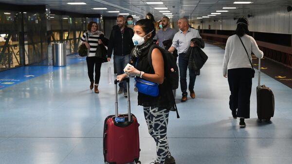 Девушка в защитной маске в международном аэропорту Барахас в Мадриде