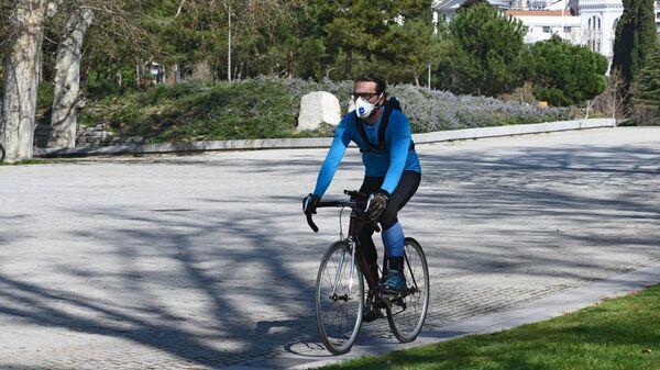 Мужчина на велосипеде в защитной маске