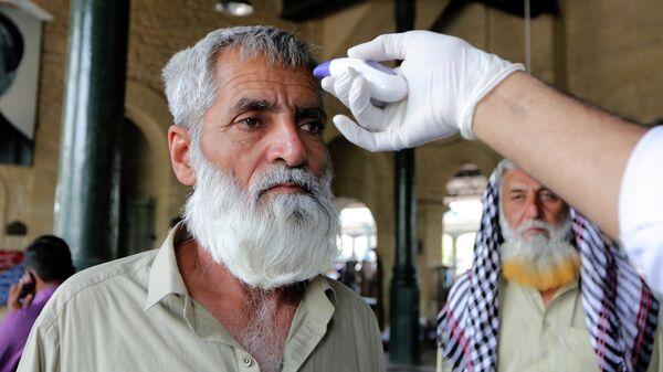 Медицинский работник проверяет температуру тела пассажира на железнодорожной станции в Карачи, Пакистан