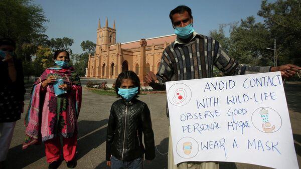 Семья держит плакат с информацией о мерах предосторожности в связи коронавирусом  перед началом мессы  в соборе Святого Иоанна в Пешаваре, Пакистан