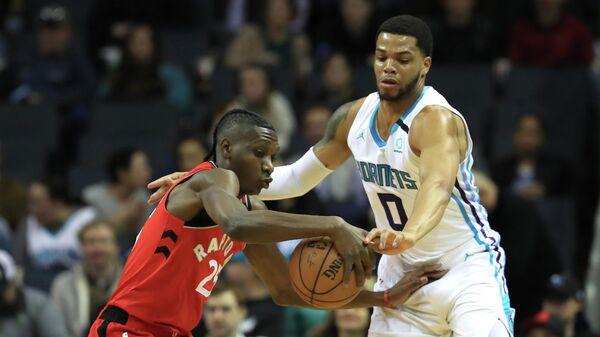 Баскетболист Торонто Рэпторс Крис Буше против Майла Бриджеса из Шарлотт Хорнетс в матче НБА