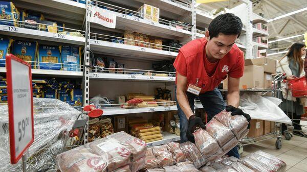 Сотрудник гипермаркета Ашан в Симферополе во время выкладки товара