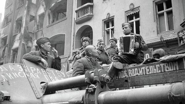 Советские солдаты слушают баян на улицах Берлина