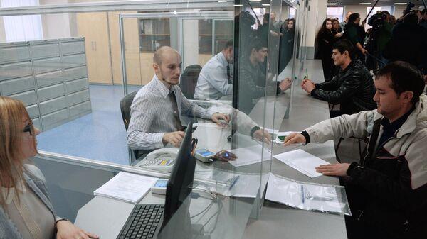 Иностранные граждане разговаривают с сотрудниками центра, получая трудовой патент в Едином миграционном центре Московской области