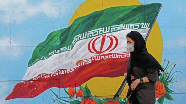 Девушка в защитной маске проходит мимо граффити с изображением национального флага в Тегеране