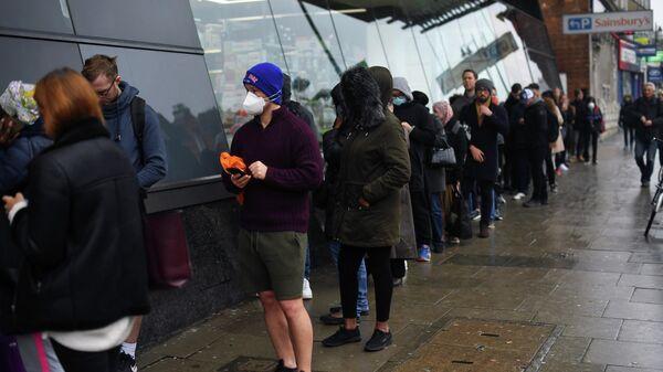Люди в очереди за покупками в магазин Sainsbury's store в Лондоне, Великобритания
