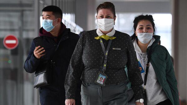 Сотрудница авиакомпании S7 и пассажиры в медицинских масках в аэропорту Толмачево в Новосибирске