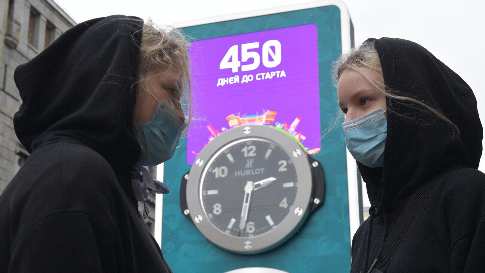 Девушки в медицинских масках рядом с часами обратного отсчета времени до старта чемпионата Европы по футболу - РИА Новости, 1920, 27.01.2021