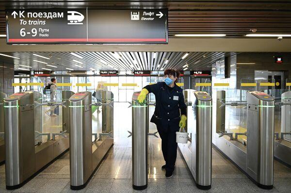 Сотрудница клининговой компании проводит дезинфекционную обработку турникетов на железнодорожном вокзале Адлера