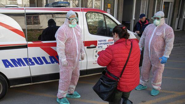 Медицинские работники в защитных костюмах и пациент в инфекционной клинике