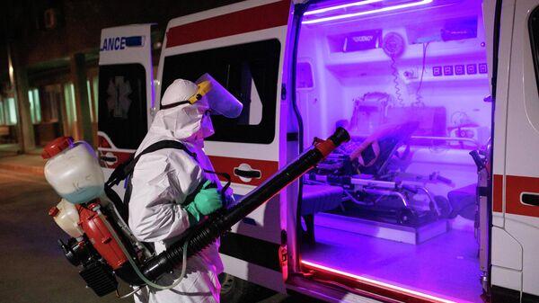 Медицинский работник в защитном костюме дезинфицирует автомобиль скорой помощи в Белграде