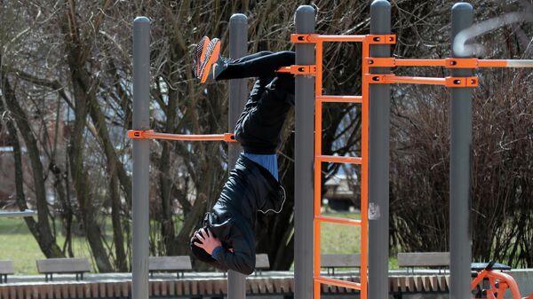 Мужчина занимается на воркаут-площадке