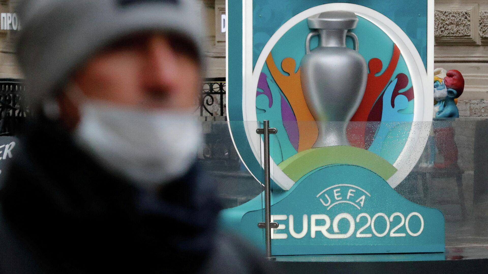 Человек в маске на фоне логотипа Евро-2020 - РИА Новости, 1920, 25.12.2020