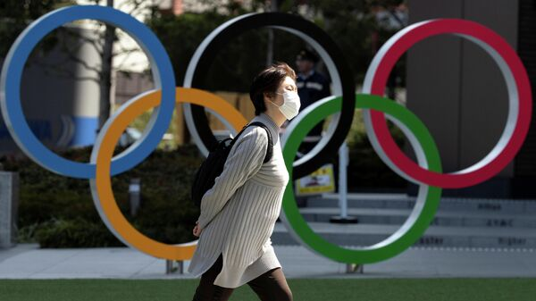 A woman wearing a protective face mask, following an outbreak of the coronavirus disease (COVID-19), walks past the Olympic rings in front of the Japan Olympics Museum in Tokyo, Japan March 13, 2020. REUTERS/Athit Perawongmetha