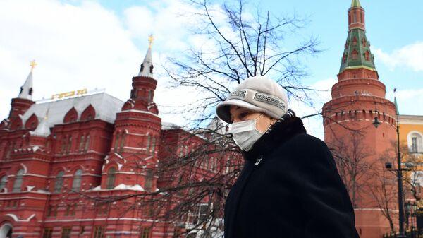 Женщина в защитной маске у стен Кремля в Москве