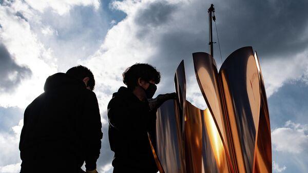 Сотрудники возле Олимпийского огня Игр-2020 в Токио