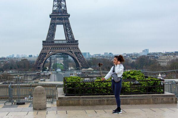 Туристка фотографируется на безлюдной площади Трокадеро у Эйфелевой башни в Париже