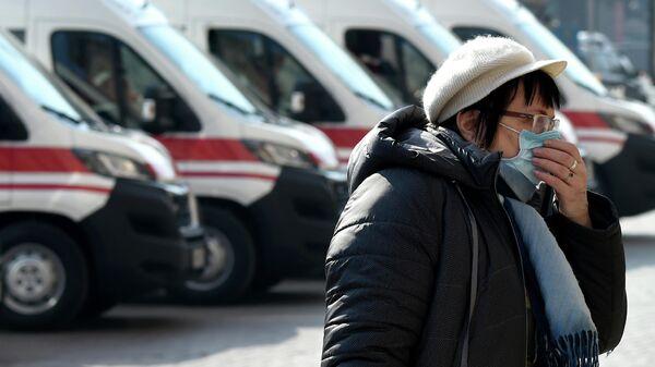 Женщина на фоне автомобилей скорой помощи в Киеве