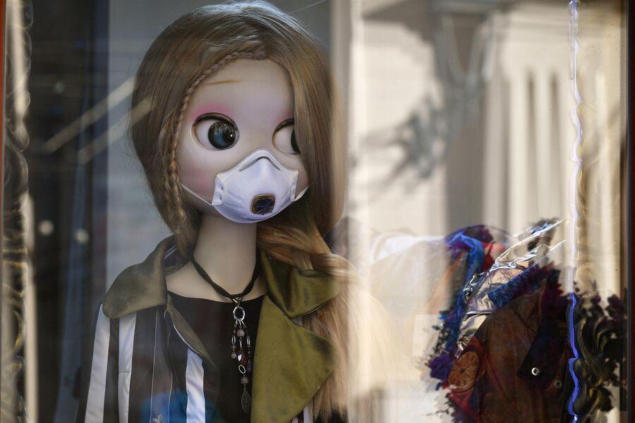 Кукла в защитной маске в витрине магазина
