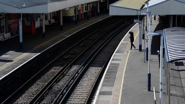 Пассажир на пустой платформе на станции Ричмонд в Лондоне