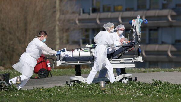 Медицинские работники везут пациента с коронавирусной инфекцией в городе Мюлуз, Франция