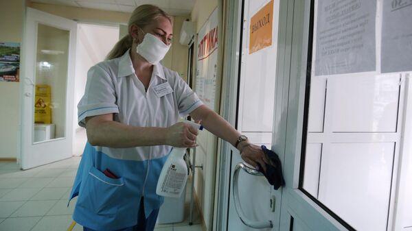 Сотрудница поликлиники дезинфицирует поверхности помещения в связи с угрозой распространения коронавируса