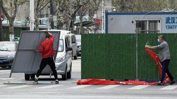 Рабочие в масках снимают барьеры на улице в Ухане, Китай
