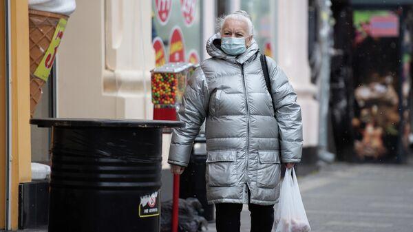 Женщина в медицинской маске идет по улице Симферополя