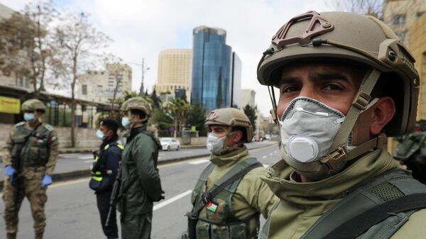 Иорданские военные в защитных масках на контрольно-пропускном пункте в Аммане
