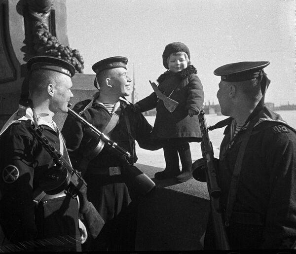 Моряки Балтийского флота беседуют с девочкой Люсей. Её и других детей вывозят из блокадного города