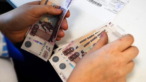 Сотрудница Почты России выдает пособие пенсионерке