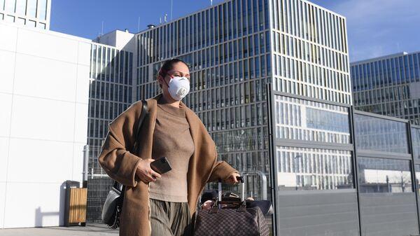 Женщина в защитной маске у здания больницы в Коммунарке