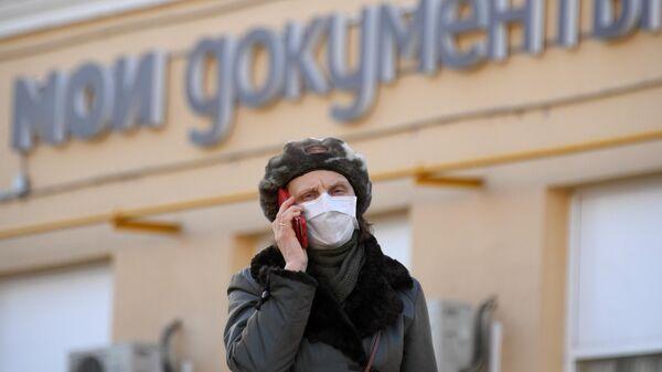 Женщина в медицинской маске около одного из центров Мои документы в Москве
