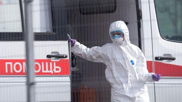 Медик проводит санитарную обработку машины скорой помощи