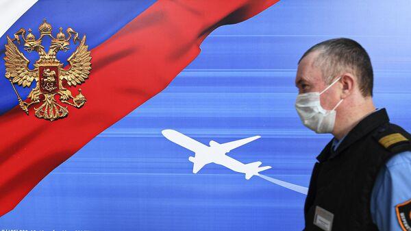 Сотрудник аэропорта Шереметьево возле билборда