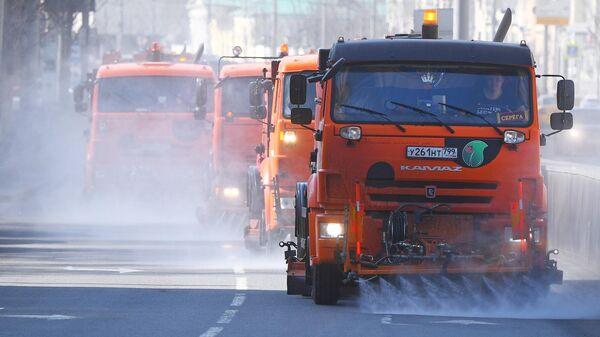 Автомобили коммунальной службы производят мытье асфальтового покрытия с использованием специального моющего средства в Москве