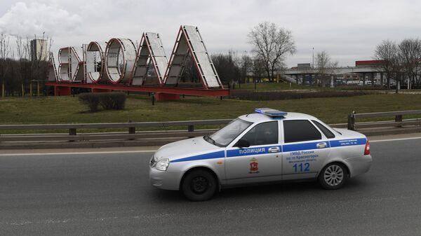 Автомобиль полиции проезжает мимо стелы на въезде в Москву