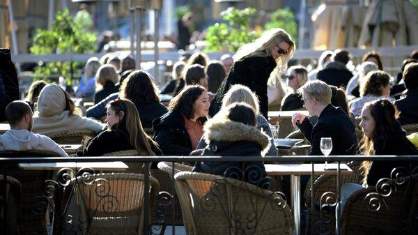 Посетители открытой веранды одного из ресторанов в Стокгольме во время пандемии коронавируса COVID-19