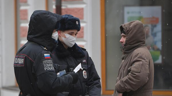 Сотрудники полиции проверяют документы прохожего на улице в Москве