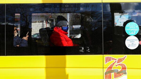 Мужчина в защитной маске в салоне автобуса