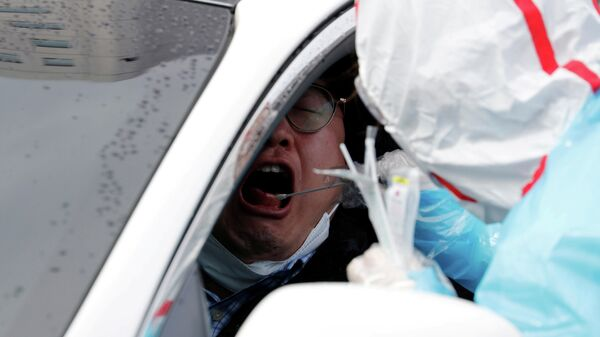 Медицинский работник делает тест на коронавирус водителю в центре Drive-Thru в Южной Корее