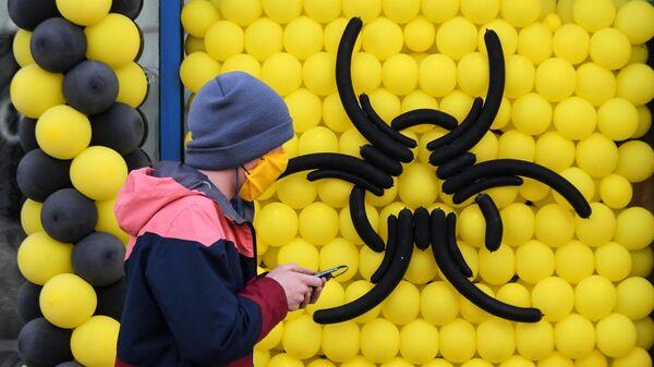 Молодой человек в защитной маске проходит мимо кафе в Москве, закрытого из-за ограничительных мер в связи с распространением коронавирусной инфекци