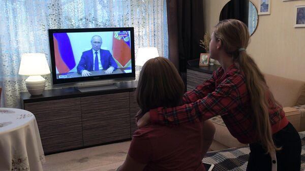 Жители Москвы смотрят трансляцию обращения президента РФ Владимира Путина к гражданам