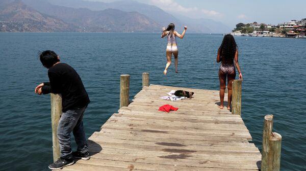 Девушка прыгает в воду в Сан-Педро-Ла-Лагуна, Солола, Гватемала