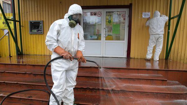 Сотрудник коммунальной службы проводит дезинфекцию у торговых рядов в городе Кировск в Ленинградской области