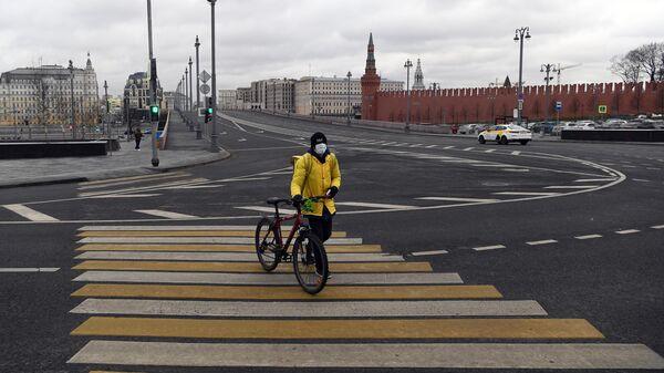 Сотрудник службы доставки Яндекс-Еда на пешеходном переходе улицы Варварка во время режима самоизоляции жителей