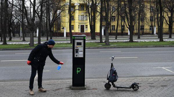 Мужчина дезинфицирует паркомат на улице в Москве