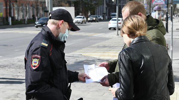 Сотрудник полиции проверяет документы у прохожих во время патрулирования улиц в целях выявления нарушителей режима самоизоляции в Ростове-на-Дону