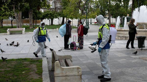 Муниципальные работники в защитных костюмах дезинфицируют площадь в Афинах, Греция